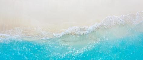 verão seascape belas ondas, água do mar azul em um dia ensolarado. vista superior do drone. vista aérea do mar, incrível fundo de natureza tropical. belo mar brilhante com ondas espirrando e conceito de areia de praia foto