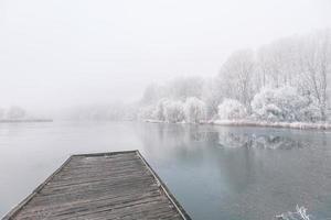 paisagem de inverno à noite. cais de madeira ao longo de um belo lago congelado. árvores com geada, cenário de inverno sazonal calmo. vista pacífica e branca foto