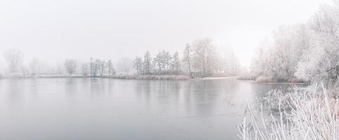 floresta de inverno no rio ao pôr do sol. paisagem panorâmica com árvores nevadas, sol, lindo rio congelado com reflexo na água. sazonal. árvores de inverno, lago e céu azul. rio gelado de neve. clima foto
