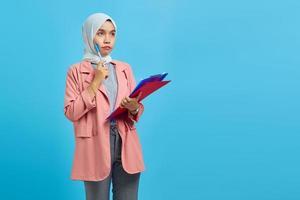 jovem mulher asiática concentrada escrevendo notas, planejando a criação de uma estratégia sobre fundo azul foto