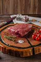 Picanha crua - picanha brasileira em uma tábua de madeira com ramo de alecrim, tomate e especiarias. foto