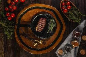 Picanha grelhada fatia cap com ramo de alecrim, garfos dourados e especiarias na tábua de madeira - picanha brasileira - vista superior. foto