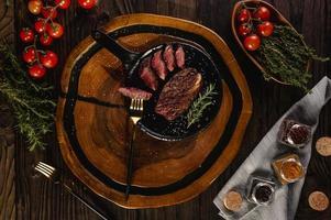fatias grelhadas cap alcatra com ramo de alecrim, garfos dourados e especiarias na tábua de madeira - picanha brasileira - vista superior. foto