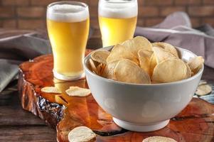 batata frita em uma tigela com dois copos de cerveja foto
