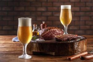 dois copos de tulipa fria suada de cerveja com bife de alcatra grelhado fatiado cap na tábua de madeira - picanha brasileira. foto