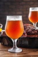 suado frio tulipa copos de cerveja ale com bife de denver grelhado na tábua de madeira - closeup. foto