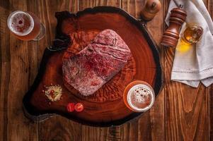 bife de denver grelhado com dois copos de cerveja na tábua de madeira. carne bovina em mármore - vista superior. foto