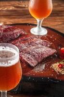 bife de denver grelhado fatiado em uma tábua de madeira com sal parrilla e dois copos de torrão suado de cerveja. Carne bovina de mármore - close up. foto