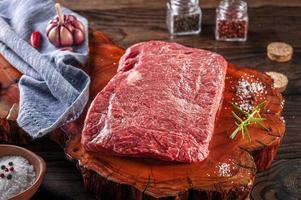 Carne crua de denver de mármore em uma tábua de madeira resinada com especiarias e ramos de alecrim. foto