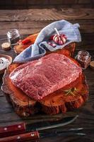 Carne crua de denver de mármore em uma tábua de madeira resinada com especiarias e garfo e faca de churrasco. foto