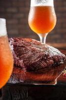 bife de denver grelhado na tábua de madeira com copos de tulipa suado de chope. carne bovina em mármore. foto