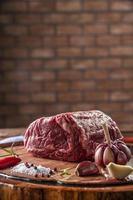 Carne de entrecosto cru em uma tábua de madeira com especiarias no fundo da parede de tijolos - close up. foto
