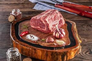 Entrecosto de carne crua em uma tábua de madeira com especiarias. foto