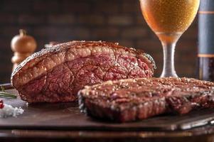 bife de alcatra grelhado fatiado cap com dois copos de cerveja na tábua de madeira. carne bovina mármore - picanha brasileira. foto