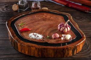 tábua de corte de madeira resinada com especiarias e garfo e faca de churrasco na mesa de madeira. foto
