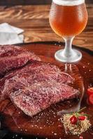 bife de denver grelhado fatiado em uma tábua de madeira com sal parrilla e copo de cerveja suado. Carne bovina de mármore - close up. foto