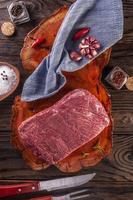 Carne crua de denver de mármore em uma tábua de madeira resinada com especiarias e garfo e faca de churrasco - vista superior. foto