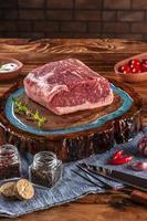 Carne de lombo crua - chouriço argentino em uma tábua de madeira resinada com especiarias. mesa de madeira com fundo de parede de tijolos. foto