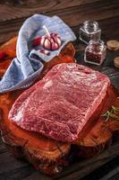 Carne crua de denver de mármore em uma tábua de madeira resinada com especiarias e alecrim foto