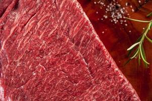 Carne de denver de mármore em uma tábua de madeira resinada com ramo de alecrim - close up. foto