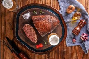 bife de alcatra grelhado com dois copos de cerveja na tábua de madeira. carne bovina em mármore - picanha brasileira - vista superior. foto