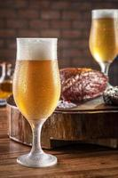 copo de tulipa frio suado de cerveja com bife de alcatra grelhado fatiado cap na tábua de madeira - picanha brasileira. foto