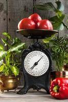 pilha de tomates vermelhos na balança de cozinha antiga foto