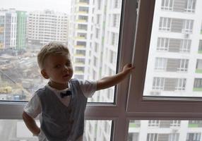 lindo menino com rosto de criança posando para fotógrafo perto da janela foto