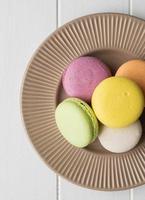 Macarons deitados planos na mesa de madeira foto