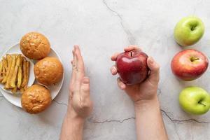 maçãs vs batatas fritas e hambúrgueres vista de cima plano plano foto