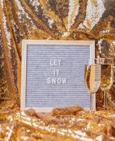 O quadro de letras de feltro deixou nevar em um fundo dourado brilhante com taças de champanhe foto