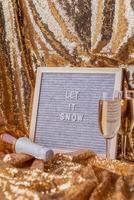 O quadro de letras de feltro deixou nevar em um fundo dourado brilhante com taças de champanhe e uma garrafa foto