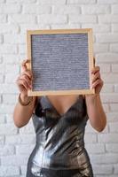 Mulher linda em um vestido de festa segurando um quadro de feltro vazio foto