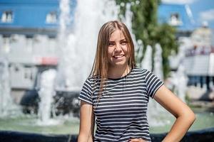 Mulher jovem caucasiana sorridente feliz com roupas casuais lá fora em um dia ensolarado perto da fonte foto