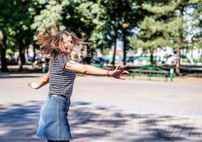 feliz mulher caucasiana em roupas casuais, sorrindo e se divertindo no parque em um dia ensolarado de verão foto