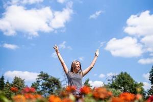 mulher sorridente feliz em um dia ensolarado na natureza no verão com as mãos abertas foto