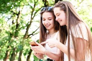 duas mulheres felizes conversando no parque usando o celular foto