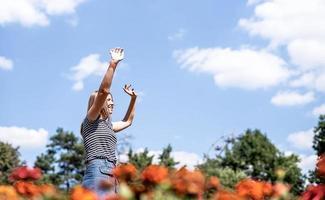 mulher sorridente feliz em um dia ensolarado na natureza no verão com os braços para cima foto