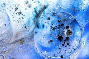 bolhas azuis brilhantes com tinta preta na superfície da água em fundo abstrato foto
