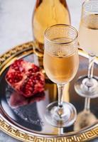 taças e garrafa com champanhe em uma bandeja foto