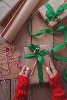 Mulher com as mãos segurando um presente de Natal embrulhado com papel ofício, fita verde e vista superior do bastão de doces na mesa de madeira foto