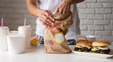 mulher com roupas de casa desempacotando comida para entrega em domicílio com hambúrgueres, caixas de macarrão e bebidas foto