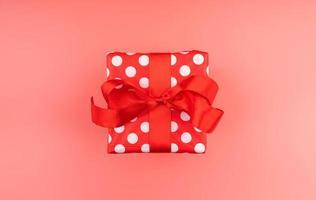 caixa de presente única vermelha com fita vermelha na vista superior do plano de fundo rosa foto