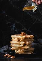 waffles belgas caseiros servidos com vista frontal de mel em fundo escuro foto