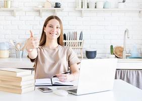 menina adolescente feliz estudando em casa mostrando o polegar foto