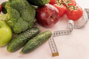 vegetais frescos e frutas para uma dieta saudável e uma fita métrica foto