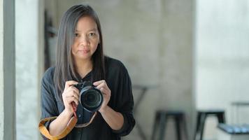 turistas asiáticos do sexo feminino segurando uma câmera para tirar fotos, o conceito de viagens de férias. foto