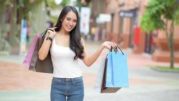 compradores femininos asiáticos carregam sacolas de compras com alegria. foto