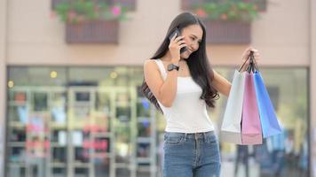 jovem compradora asiática está usando um smartphone e olha para a sacola de compras na mão. foto