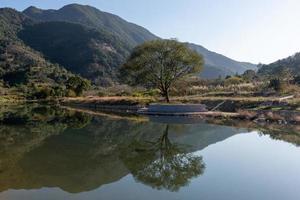 o rio do país reflete a montanha, e as aldeias e florestas estão sob o céu azul foto